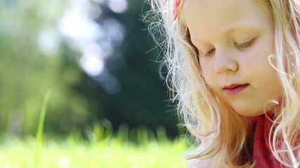 little girl inflates soap bubbles in the park - dolly shot