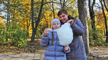 mother with teen daughter standing eat cotton candy in park