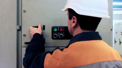 engineer turns on electrical equipment of control panel