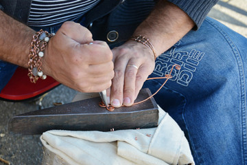 Craftsman bends copper wire