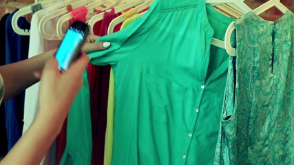 Woman doing shopping and taking photo of green shirt by phone