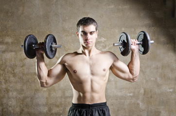 Young man training weights in old gym, shoulder exercise