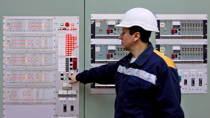 engineer checks light indication on two control panels