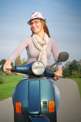 Young female riding vespa scooter happy