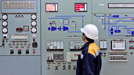engineer checks light indication on main panel of station