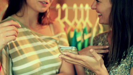 Happy women looking on smartphone in the boutique and chatting