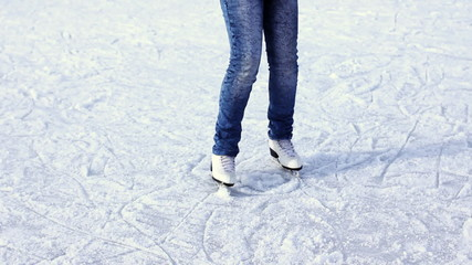 legs teenage girl who rotating on skating rink in winter