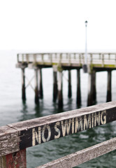 No swimming sign on pier fence. Coney Island.