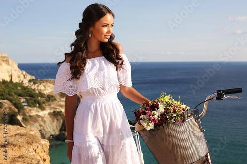 Fototapeta beautiful smiling girl riding a bicycle along the sea coast