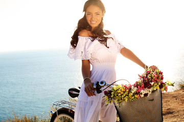 pretty girl with dark hair in elegant dress sitting on bicycle