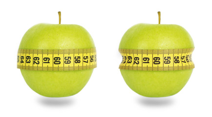 Two green apples and yellow measuring tape
