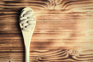 Vitamins or supplements in wooden spoon on vintage wooden board