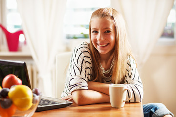 Teenage girl with laptop, at home