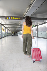 woman pulling suitcase at airport