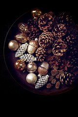 Pine cones and Christmas ornaments on a rustic tray