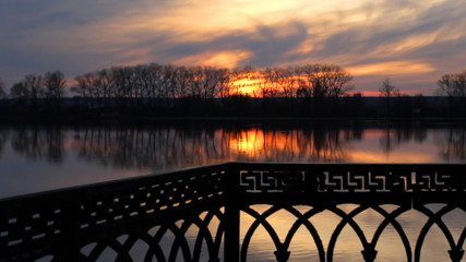 timelapse sunset at city lake near forged fence in spring