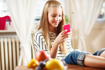 Teenage girl texting message, on mobile phone, at home