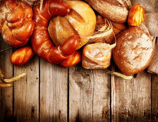 Various Bread and Sheaf of Wheat Ears over Wood Background