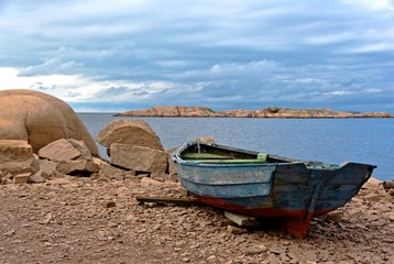 Red granite boulders and a rowing boat.