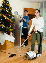 Couple cleaning with vacuum cleaner