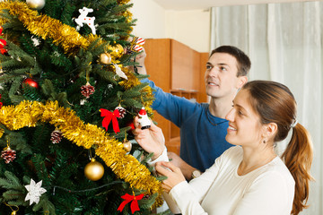Couple decorating Christmas tree