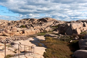 Red granite boulders and blue cloudy sky.