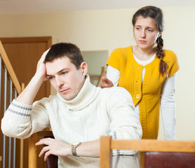 Family conflict. Upset ordinary man against sadness woman  at ho