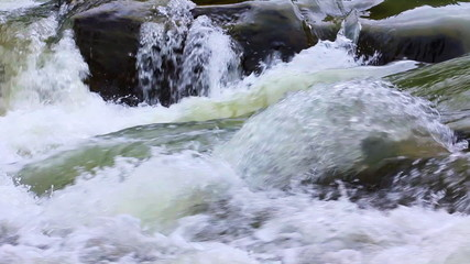 small waterfall and boiling water of mountain river, closeup