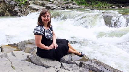 pretty woman sits on stone by shore of mountain river