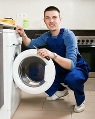 Repairman repairing washing machine