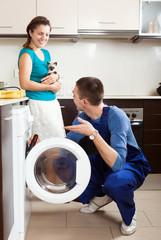 Repairman repairing a washing machine for young  woman