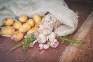 Potatoes and garlic in canvas sack on rustic wooden table