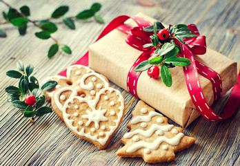VintagecChristmas gift box and gingerbread cookies on wooden bac