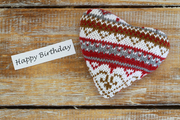 Happy birthday card with knitted heart on rustic wooden surface