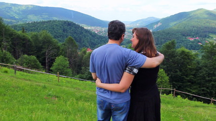 loving couple stands embracing and looks at beautiful view