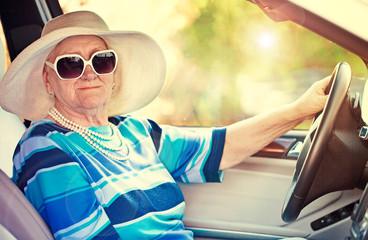 senior woman in sunglasses driving automobile
