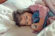 Leinwanddruck Bild - cute little girl sleeping with stuffed toy