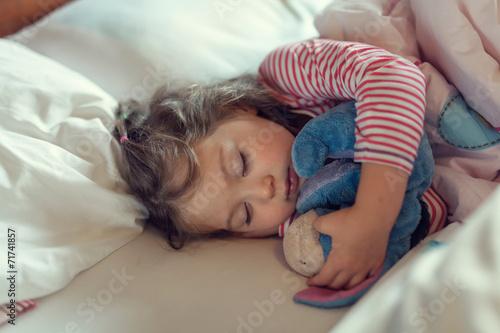 Leinwanddruck Bild cute little girl sleeping with stuffed toy