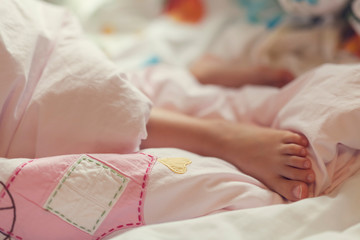 feet of sleeping child in bed