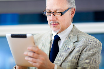 Senior businessman using his tablet