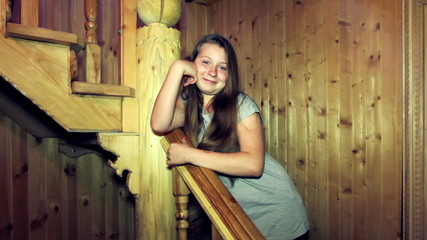 girl stands and smiles leaning on railing wooden stair in house