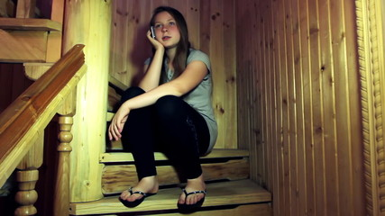 cute teen girl listen cell phone sitting on wooden stair in home