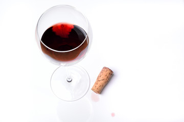 A glass of red wine with cork on a white background