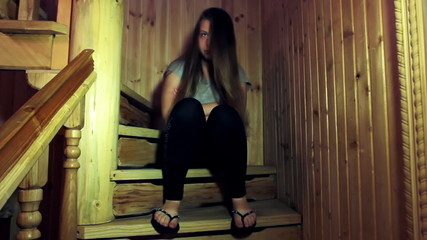 sad teen girl sits on wooden stairs in home