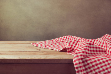 Empty wooden deck table with checked tablecloth