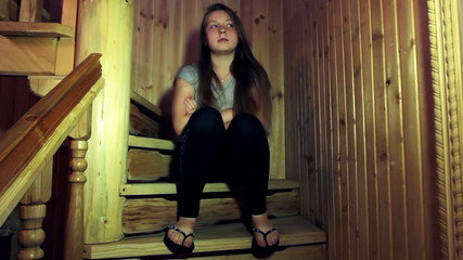 sad teen girl sits and looks around on wooden stairs in home