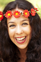 Beautiful woman with a wreath of red flowers on her head in a pa