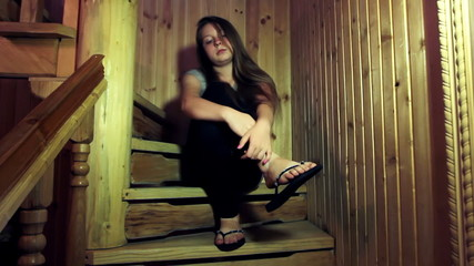 nice teen girl sits sad on wooden stairs in home