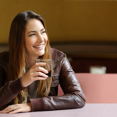 Happy pensive woman refreshing with a drink in a restaurant