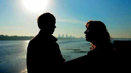 guy with his mother near wide river, silhouette against sunrise